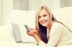 smiling businesswoman with laptop and credit card